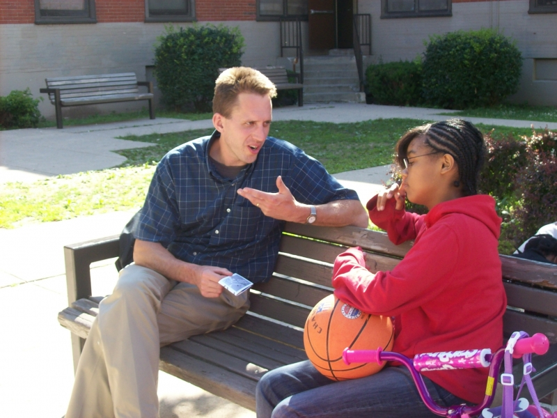 Aaron sharing a gospel booklet with a girl after the meeting.