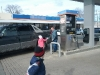 Gabriella gives a packet to a man at a gas station.